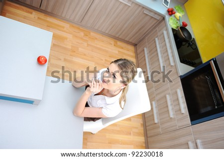 Young   woman in kitchen sitting on chair
