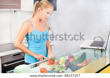 Young woman in kitchen with laptop - stock photo