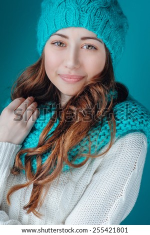 young woman in knit scarf and hat mint color.