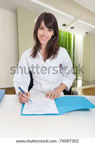 Young woman in lab coat sitting on a desk in a zen interior