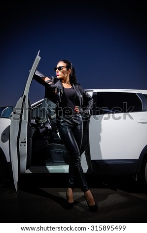 Young woman in leather clotes with car - stock photo