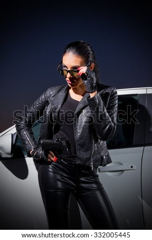 Young woman in leather clothes with car - stock photo