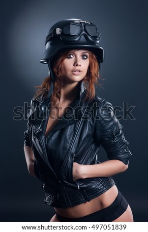Young woman in leather jacket and helmet on a studio background