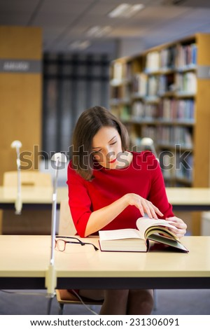 Young woman in library found something very interesting - stock photo