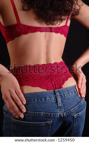 Young woman in lingerie is taking her jeans off - stock photo