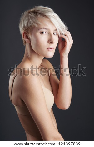 Young woman in lingerie isolated against dark background. Beauty portrait. - stock photo