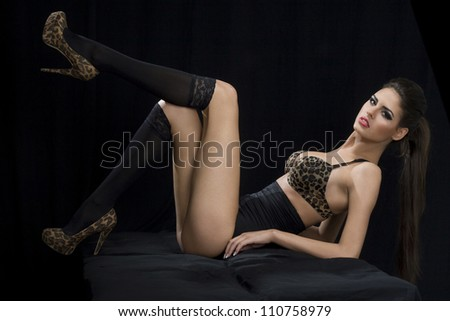 Young woman in lingerie on dark background - stock photo