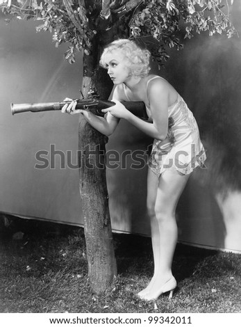 Young woman in lingerie pointing a musket at her suspect - stock photo