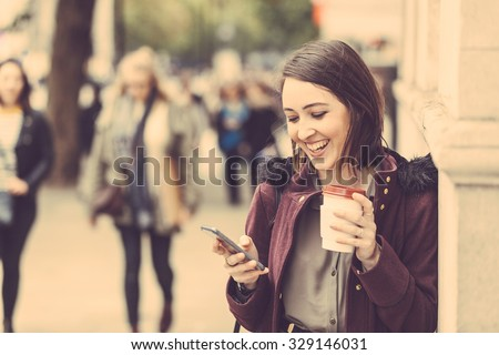Young woman in London standing by the sidewalk, holding a cup of tea and typing on her smart phone. It is a cloudy winter day, and there are many blurred persons on background. - stock photo