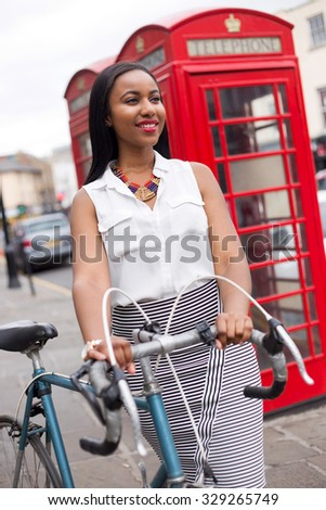 young woman in London with a bicycle - stock photo