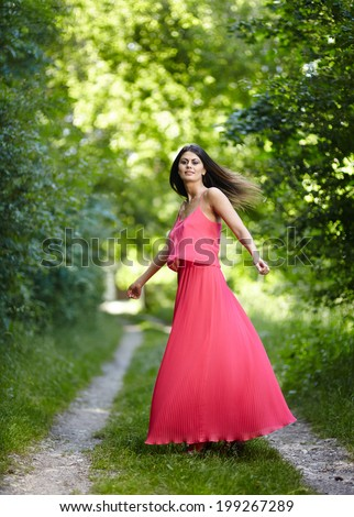 Young woman in long red dress jumping and dancing outdoor in a park