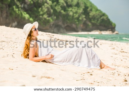 Young woman in long white dress and hat leying on white sand of tropical beach having great summer time on holidays. Summer vacation, holidays, serenity, travel, lifestyle concept