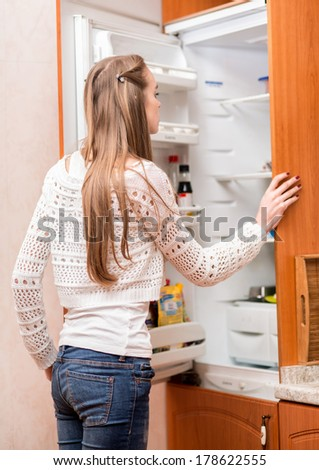 Young woman in looking to the fridge - stock photo