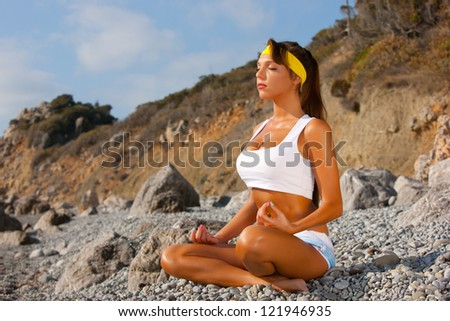 Young woman in lotus pose meditating - stock photo