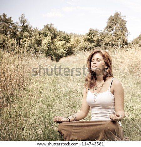 Young woman in lotus position in a sunny field - stock photo