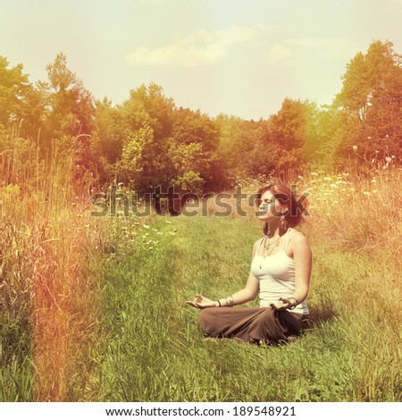 Young woman in lotus position meditating in nature, instagram style - stock photo