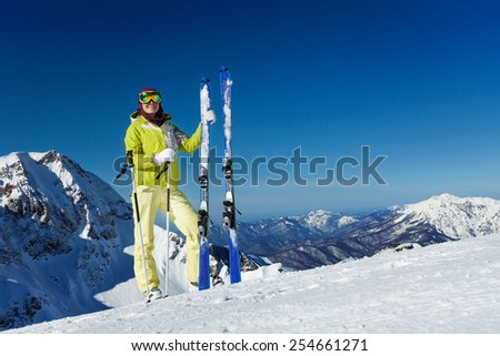 Young woman in mask stands and holds ski, poles - stock photo