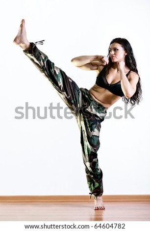 Young woman in military clothes kicking. - stock photo
