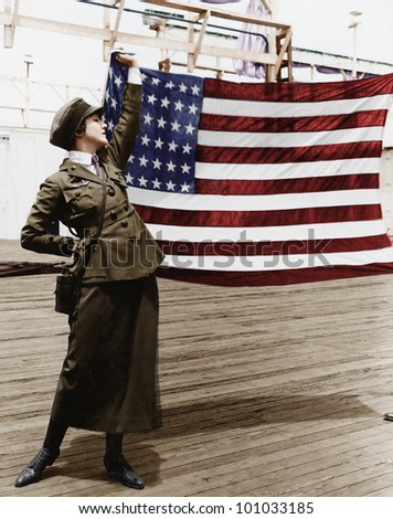 Young woman in military uniform holding up an American flag - stock photo