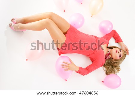 young woman in mini dress lying down on floor with pink balloons - stock photo