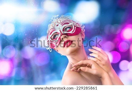 Young woman in mysterious venetian carnival red mask in front of night city illumination - stock photo