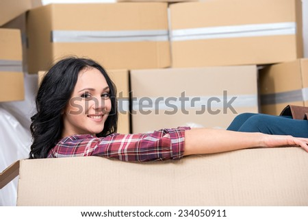 Young woman in new apartment in a cardboard box is looking at the camera. - stock photo