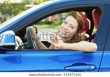 Young woman in new car showing blank drivers license or sign out, through side car window. Happy lovely female model driver enjoying her new auto outside parking lot. Positive face expression, emotion - stock photo