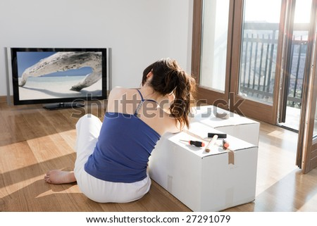 young woman in new house leaning on cardboard box and watching television - stock photo