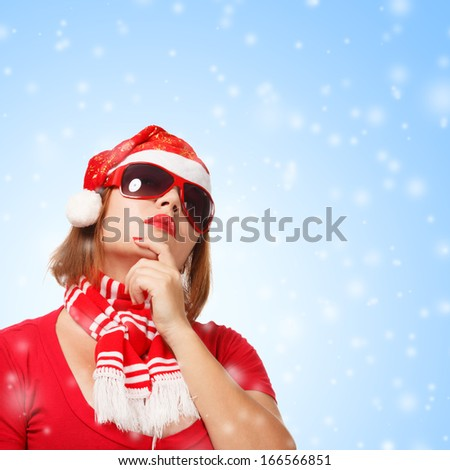 Young woman in new year or christmas suit and glasses smiling on blue background with snowfall - stock photo