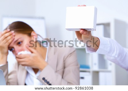 Young woman in office holding a pack of medicine - stock photo