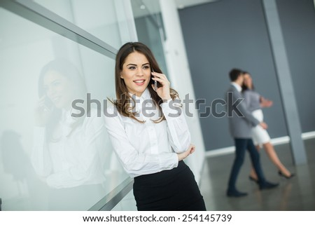 Young woman in office with mobile phone - stock photo