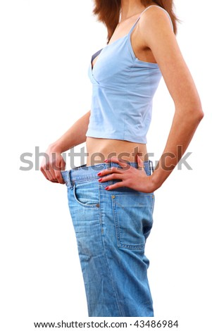 young woman in old jeans pant after losing weight - stock photo