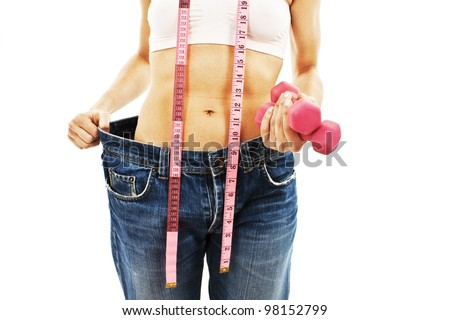 Young woman in old jeans pant after losing weight. Isolated on white background. - stock photo
