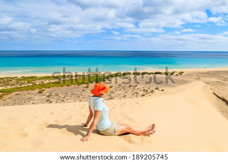Young woman in orange hat sitting in sand on a dune looking at Sotavento beach on Jandia peninsula, Fuerteventura, Canary Islands, Spain