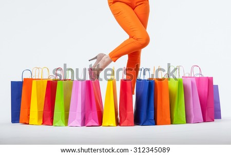 Young woman in orange pants with shopping bags, white background - stock photo