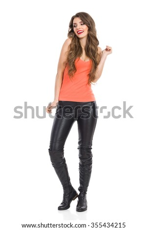 Young woman in orange shirt, leather trousers and boots standing and looking away. Full length studio shot isolated on white. - stock photo