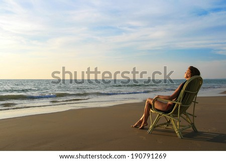 Young woman in orange swimwear sitting on the wicker chair - stock photo