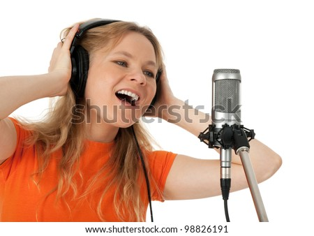 Young woman in orange t-shirt singing with studio microphone. Isolated on white background.