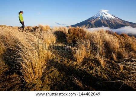 Young woman in outdoor scenery with volcano in the background - stock photo