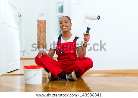 Young woman in overalls renovated because she moved to their new or old home - stock photo