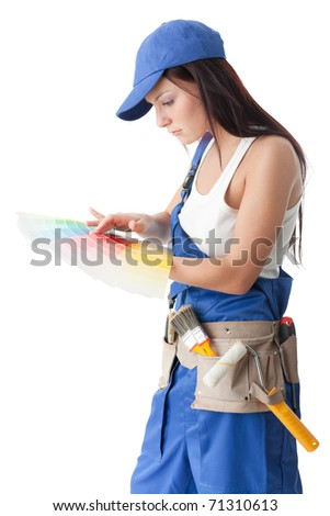 Young woman in overalls with a color guide and paintbrush on a white background. - stock photo