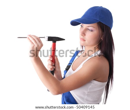 Young woman in overalls with hammer and nail on a white background.