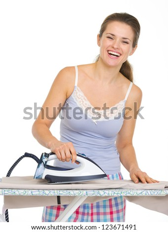 Young woman in pajamas ironing - stock photo