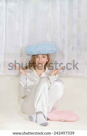 Young woman in pajamas sitting and holding pillow  - stock photo