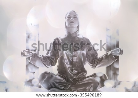 Young woman in pajamas sitting in the lotus position and meditating. Morning meditation and exercises. Yoga classes.