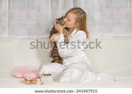 Young woman in pajamas with a cat - stock photo
