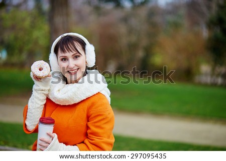 Young woman in Paris with take-away coffee and pastry, having a picnic near the Eiffel tower - stock photo