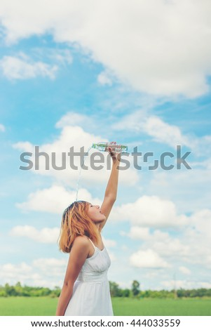 Young woman in park pours over a face for freshing at grassland enjoy and happy life.