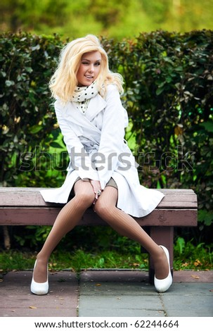 Young woman in park sitting on bench and winking. - stock photo