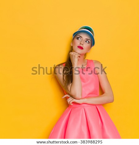 Young woman in pink dress and blue sun visor posing with hand on chin and looking up. Three quarter length studio shot on yellow background. - stock photo